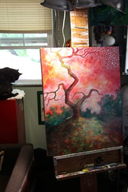 "Tobin supervising my progress from her window perch. I am working on one of my favorite areas on the painting, the upper right corner. I had asked about using glitter on the piece, and was nicely told to hold the glitter. I enjoy working with people on commission pieces because it challenges me to go outside my comfort zone, etc., but the more I stared at that upper right corner the more I knew it NEEDED glitter. One evening, agonizing over the situation, Mark turned to me and said ""Stop being a pussy and put glitter on it!"" After I recovered from my fits of laughter, the red glitter began to flow and I was very happy. On top of that surface, I painted the cell forms so that the glitter became pulsing lines of color peeking around the opaque paint. When I presented the piece, I explained the situation and they immediately said they loved the glitter, so my little glitter rebellion paid off."