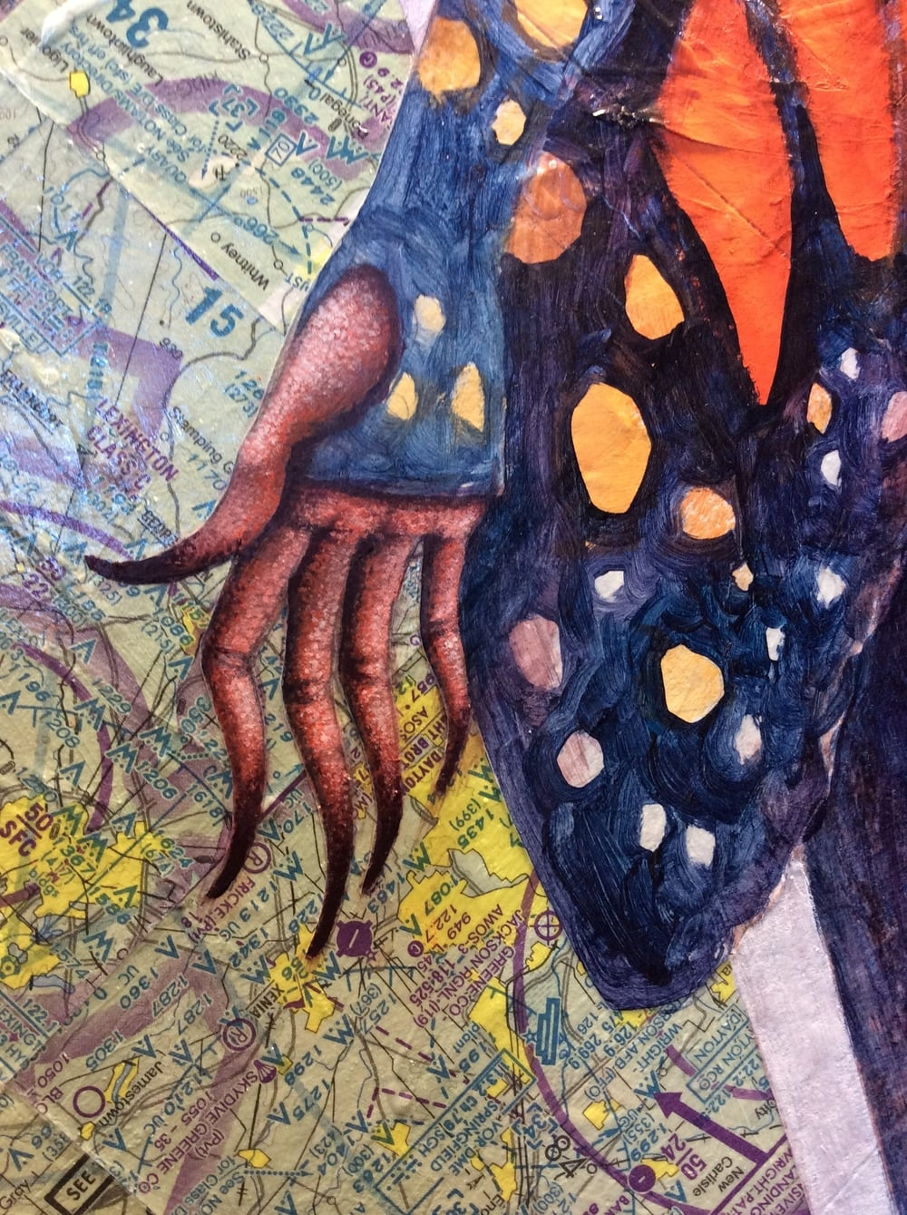 A detail of the hands in progress and the maps.