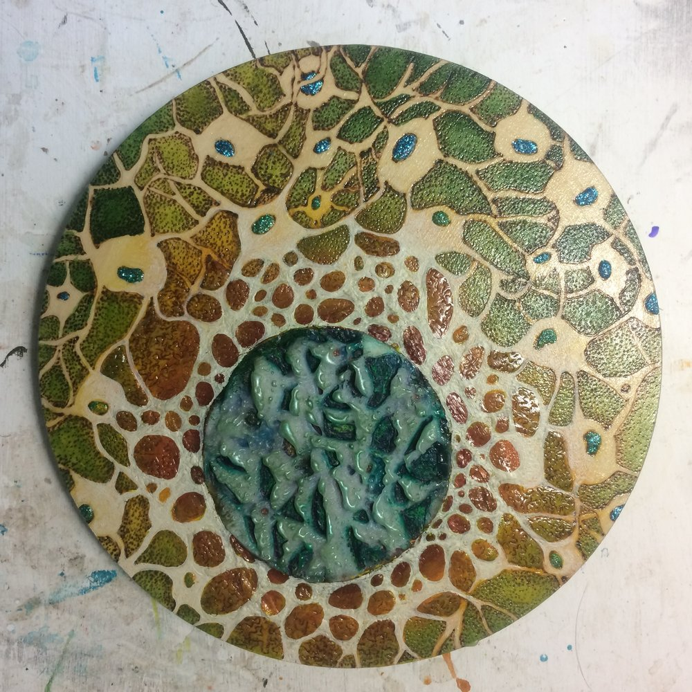 (A) Cut square into circle, reverse painted pebbles. (K) Added jute around edge, green pastel. (A) Tied knot.