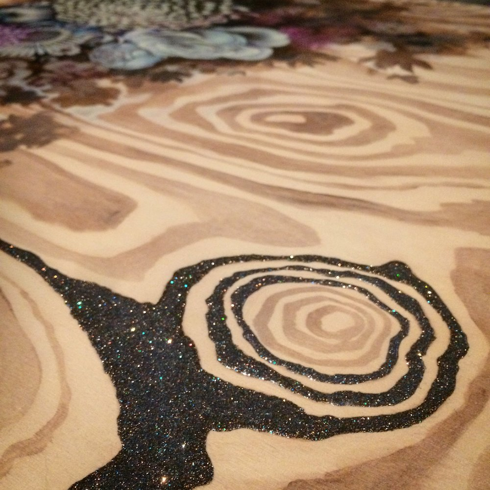 Adding glitter mixed with pouring medium to wood grain.