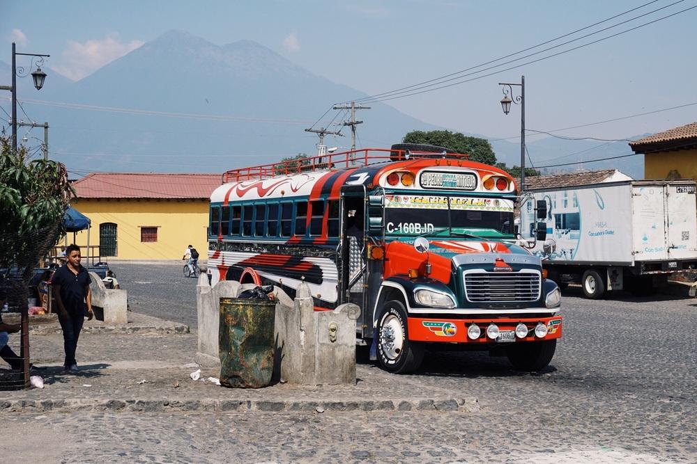 Ein typischer Chicken-Bus und im Hintergrund der Vulkan Acatenango.