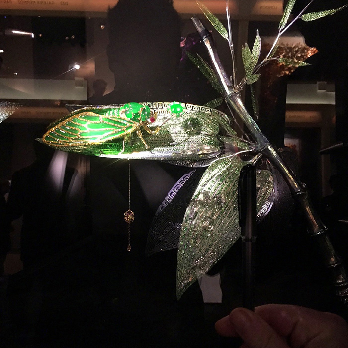 Jewelled cicada sculpture by Wallace Chan, in jadeite, diamonds and emeralds.  Note the scale of the hand in the foreground to the piece itself.