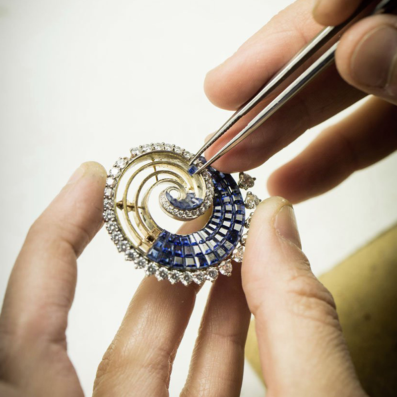 A skilled VC&A craftsman slides the specially cut stones onto the rails of this brooch to create the illusion of invisible setting.