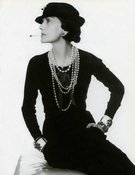 Coco Chanel wearing her trademark pearls, Verdura cuffs and signature cigarette.