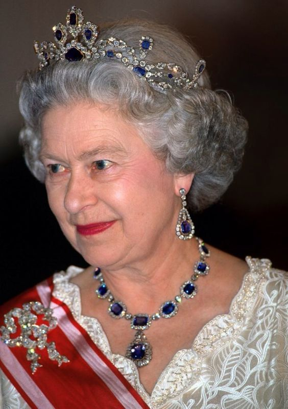 Queen Elizabeth II wearing the sapphire and diamond earrings and necklace her father gave her to mark her wedding to Prince Philip in 1947.