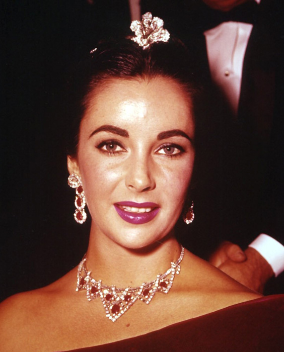 A youthful Elizabeth Taylor wearing the Cartier earrings and necklace to an event.  With her ususal panache, she is wearing a diamond flower in her hair.