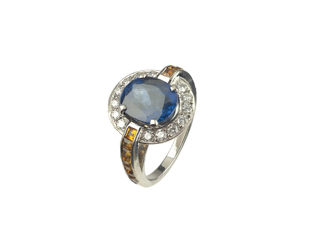 A client's own sapphire set into a bespoke setting of diamonds, citrine and white gold.