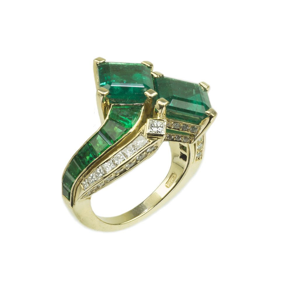 An important Columbian emerald and diamond ring, each of the beautifully matched stones being over 2 carats each.  The curved stones on the stand were specially cut to fit the mount by craftsmen in Germany.
