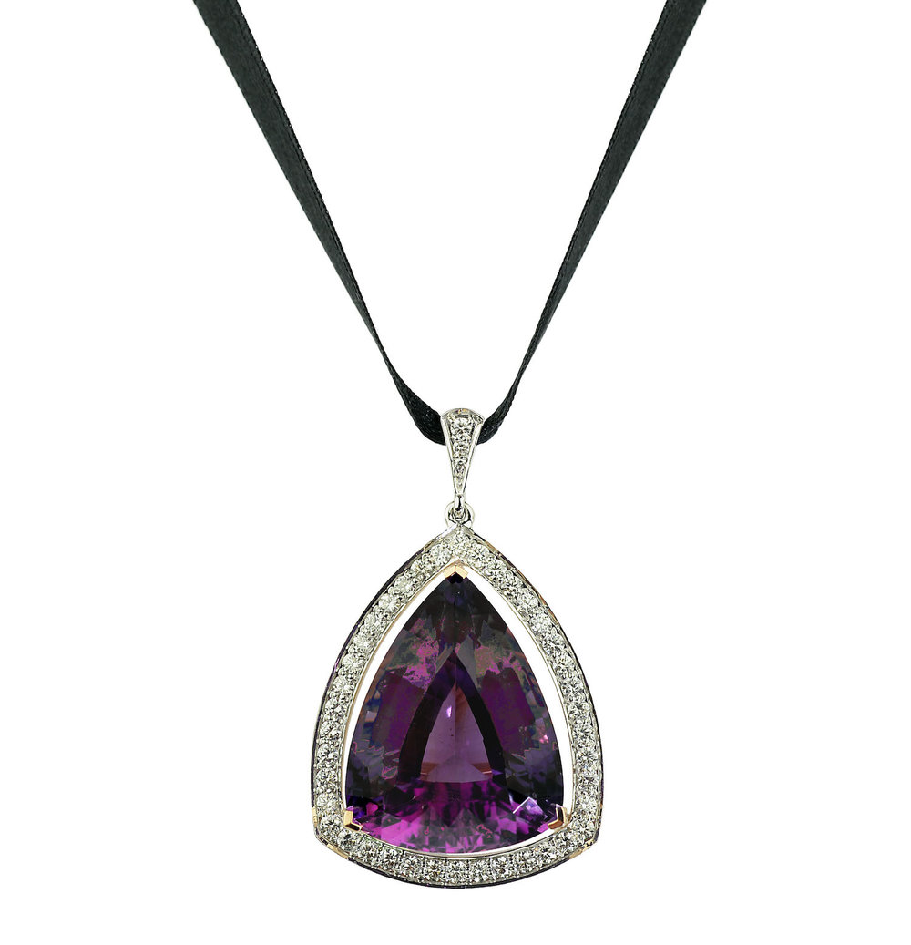A fancy cut amethyst pendant set with diamonds, suspended from black silk.