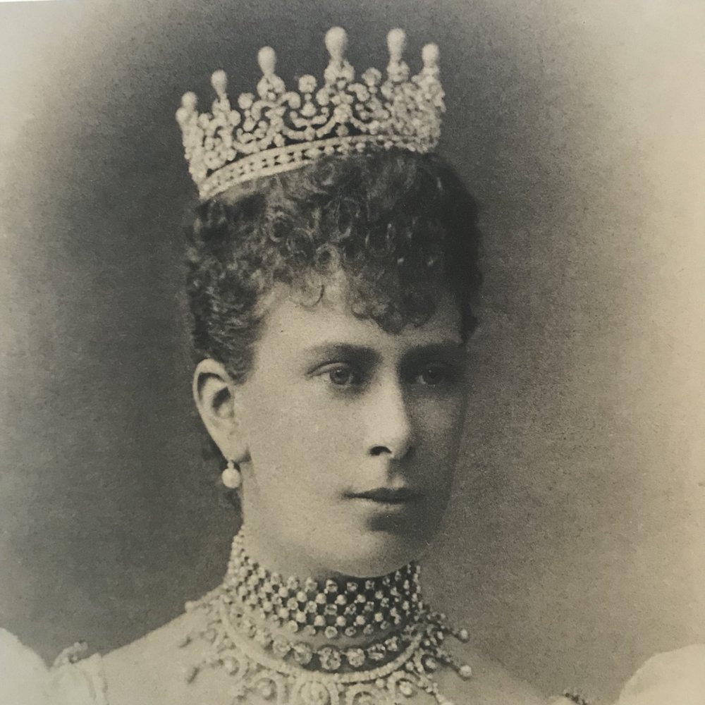 Queen Mary wearing the tiara given to her by the Ladies of Great Britain as a wedding present.  She removed the upright pearls to create the Lover's Knot tiara.