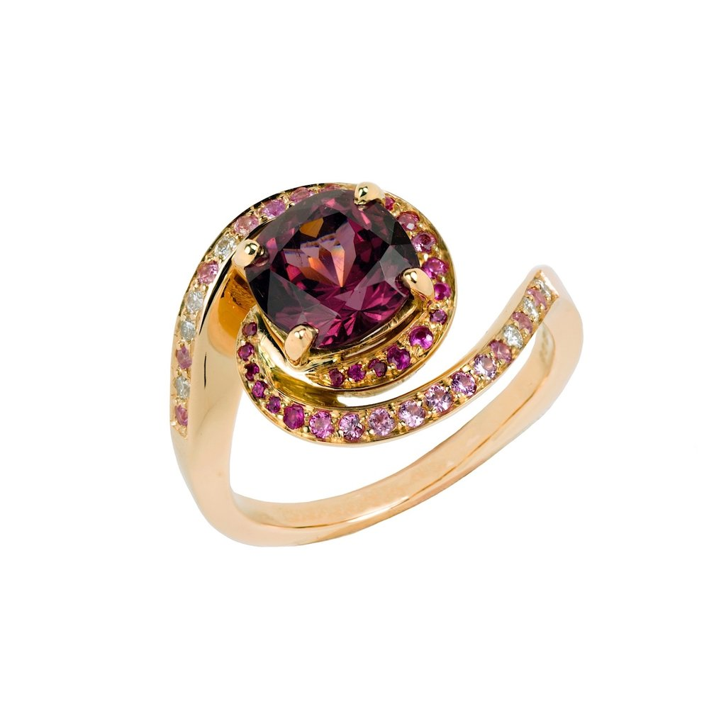 Galaxy ring with a rhodolite garnet as the centre stone, set in rose gold.  It was inspired by the swirling pattern of galaxies in the night sky.  Note how the stones surrounding the central gem have been colour graded.