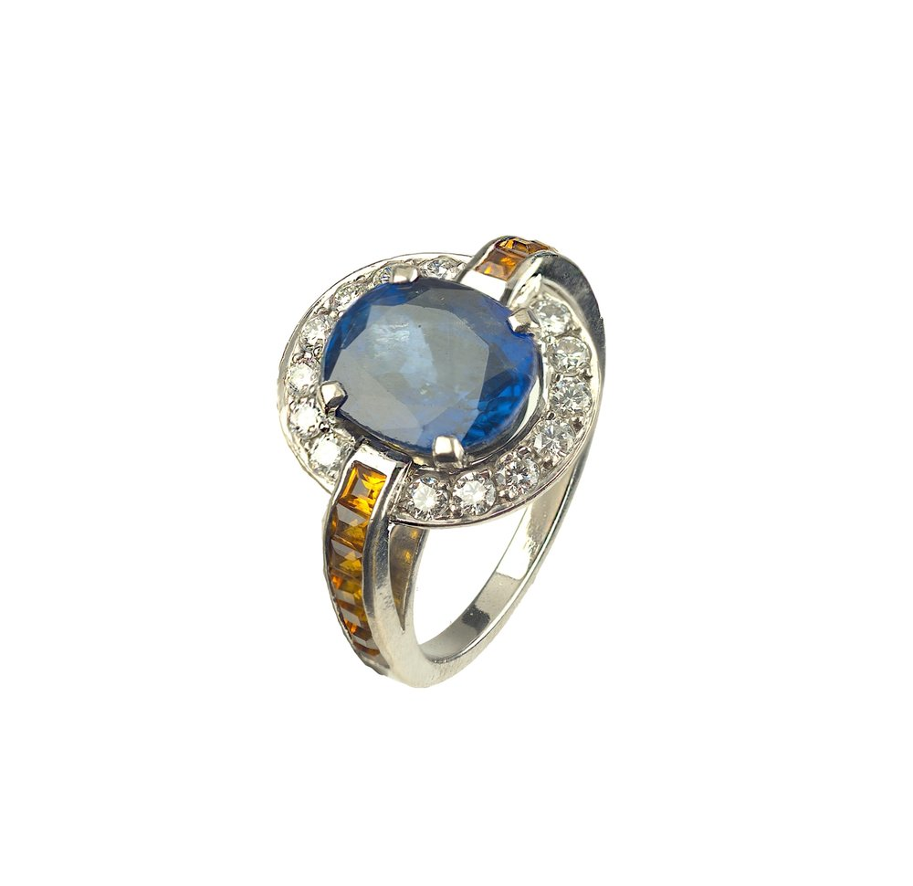 An Art Deco style ring in white gold set with a large central sapphire, surrounded by diamonds and set with citrine shoulders.