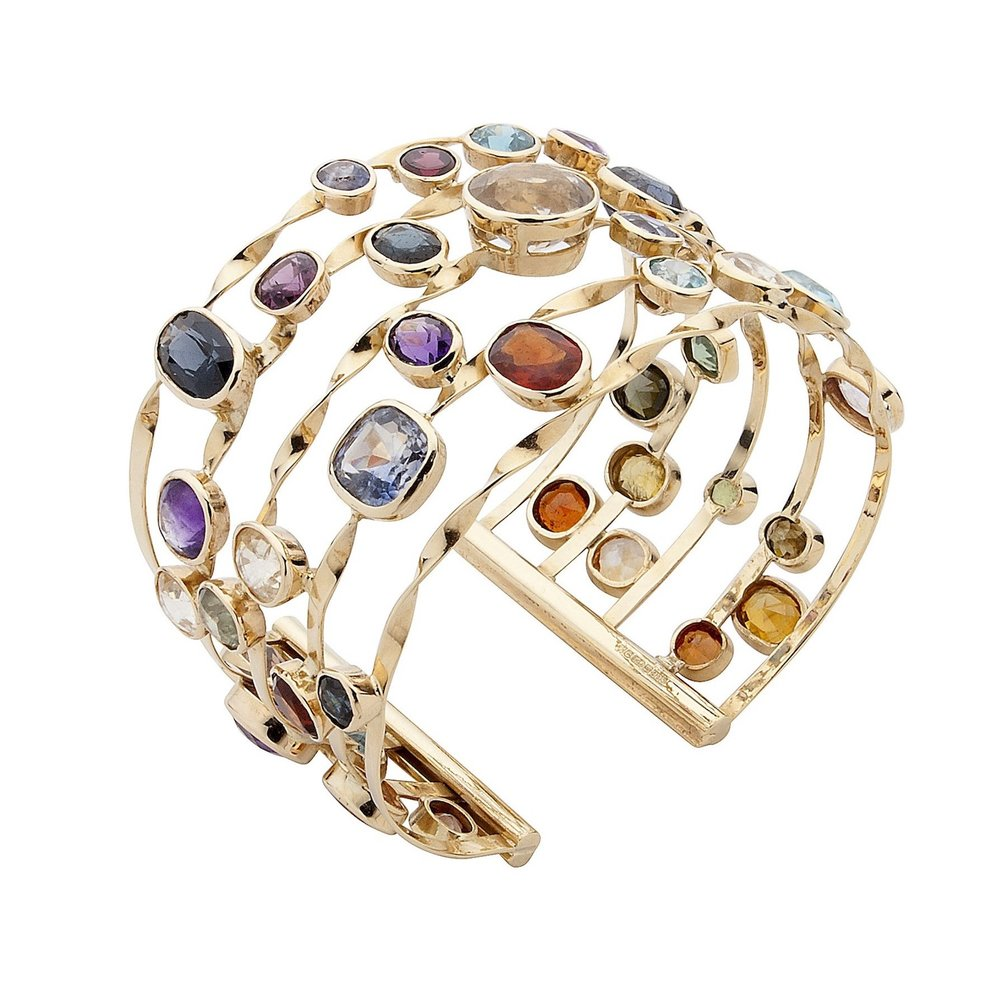 A gold cuff bracelet set with multi coloured sapphires and zircons.