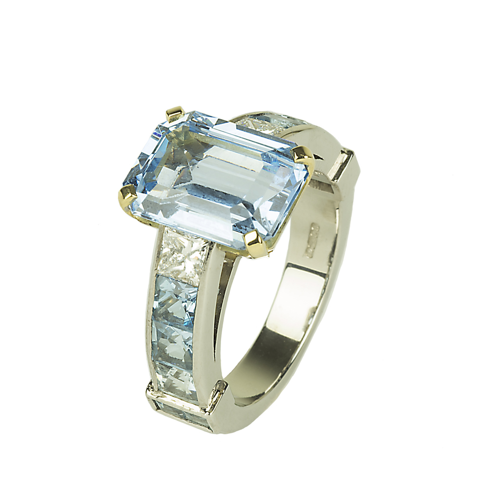 An emerald cut aquamarine and diamond ring with diamond and aquamarine shoulders.