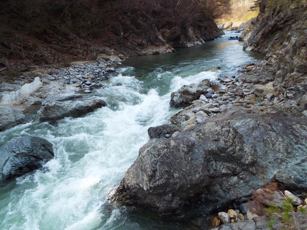 划行在大自然中,溪流一閃一閃地,兩旁樹木綿延,橋上的人們開心地朝船隻揮手。
