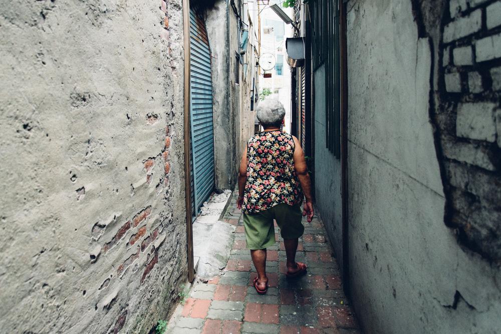 穿梭大街小巷中的米店阿嬤很不好意思地看著鏡頭說:「我走路不好看啦。」