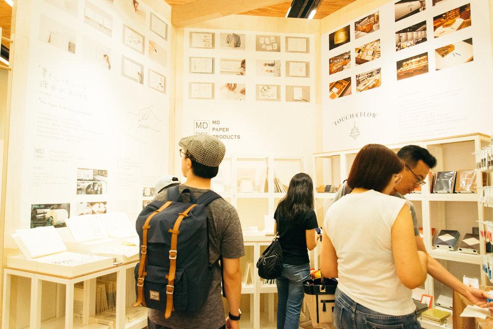 日本文具品牌「MIDORI」,其熱銷系列TRAVELER's notebook擁有海內外許多擁護者;右邊則是日本選品店「TOUCH& FLOW」所帶來的原創文具商品,經過現場觸摸、觀察,才能感受出其筆記本上精細的燙金設計。