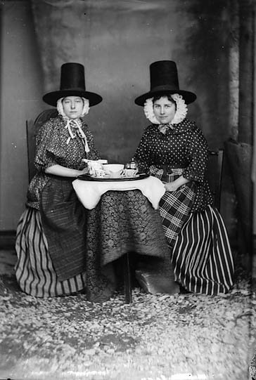 Two_women_in_national_dress_drinking_tea_(Jones)_NLW3363089.jpg