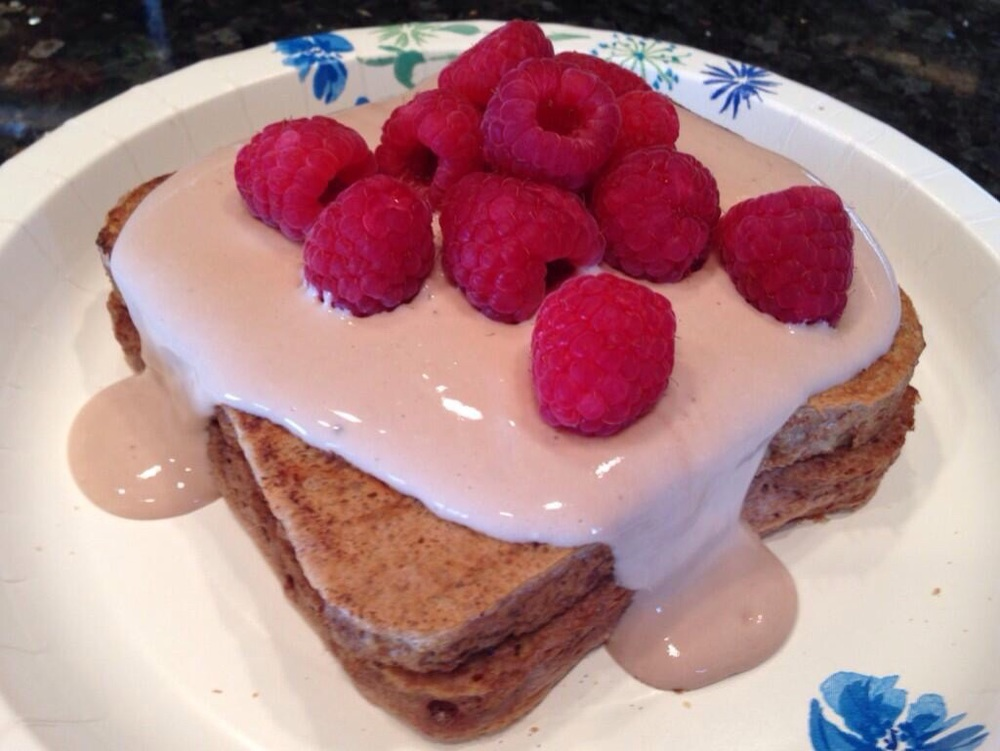 This topping is greek yogurt, almond milk and chocolate protein powder with raspberries.