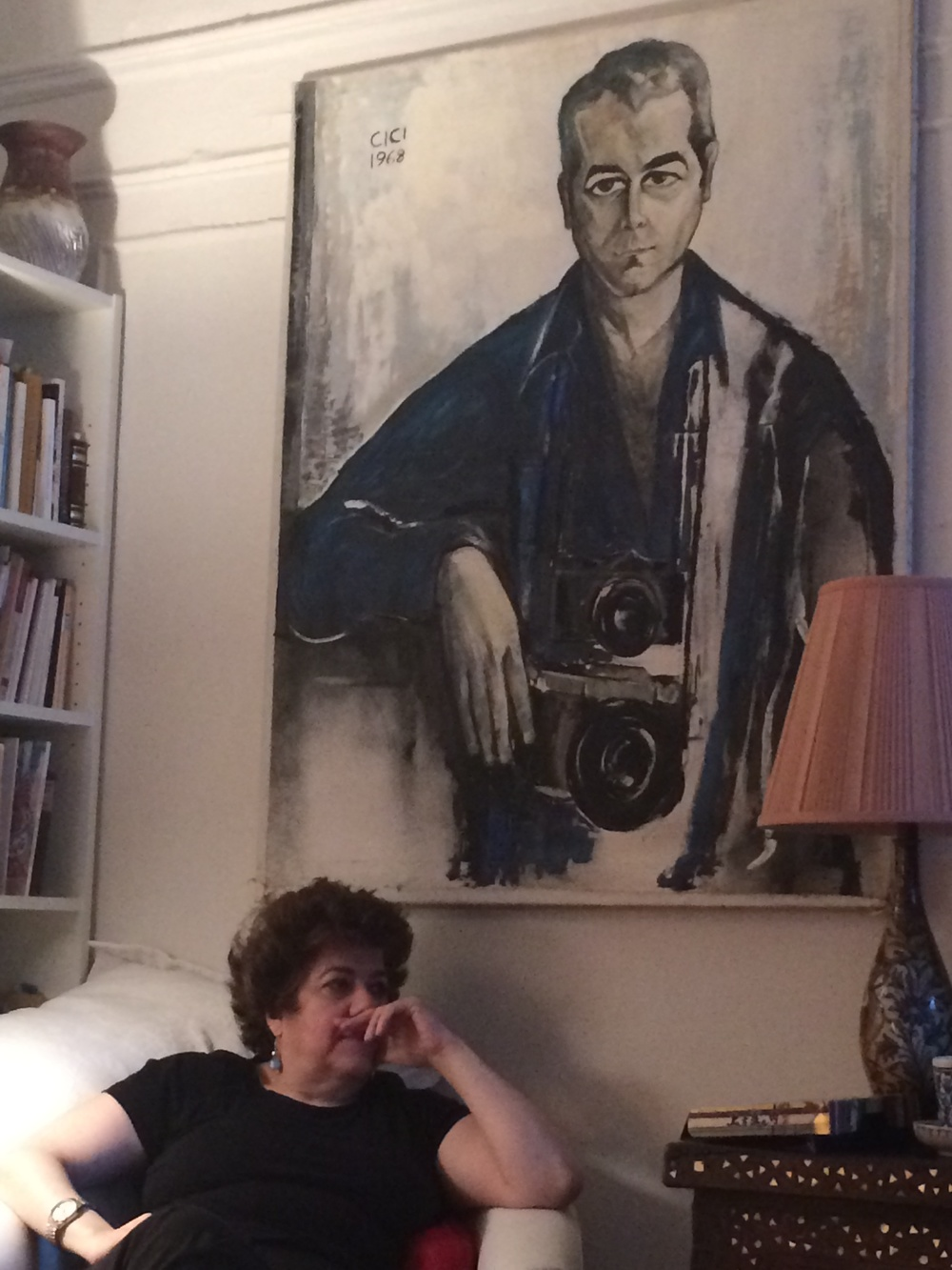Lola Koundakjian, sits beneath a portrait of her father in her New York City home. Photo courtesy of Koundakjian.