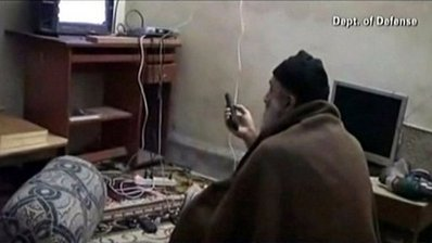 Osama bin Laden watching TV at his compound in Pakistan by U.S. Federal Government. Licensed through Wikimedia Commons.