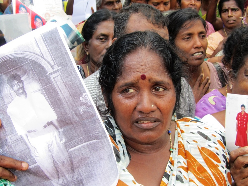 a tamil woman tearfully holds up photographs of her disappeared loved ones at a demonstration in jaffna in december 2011. image courtesy of tamil guardian.