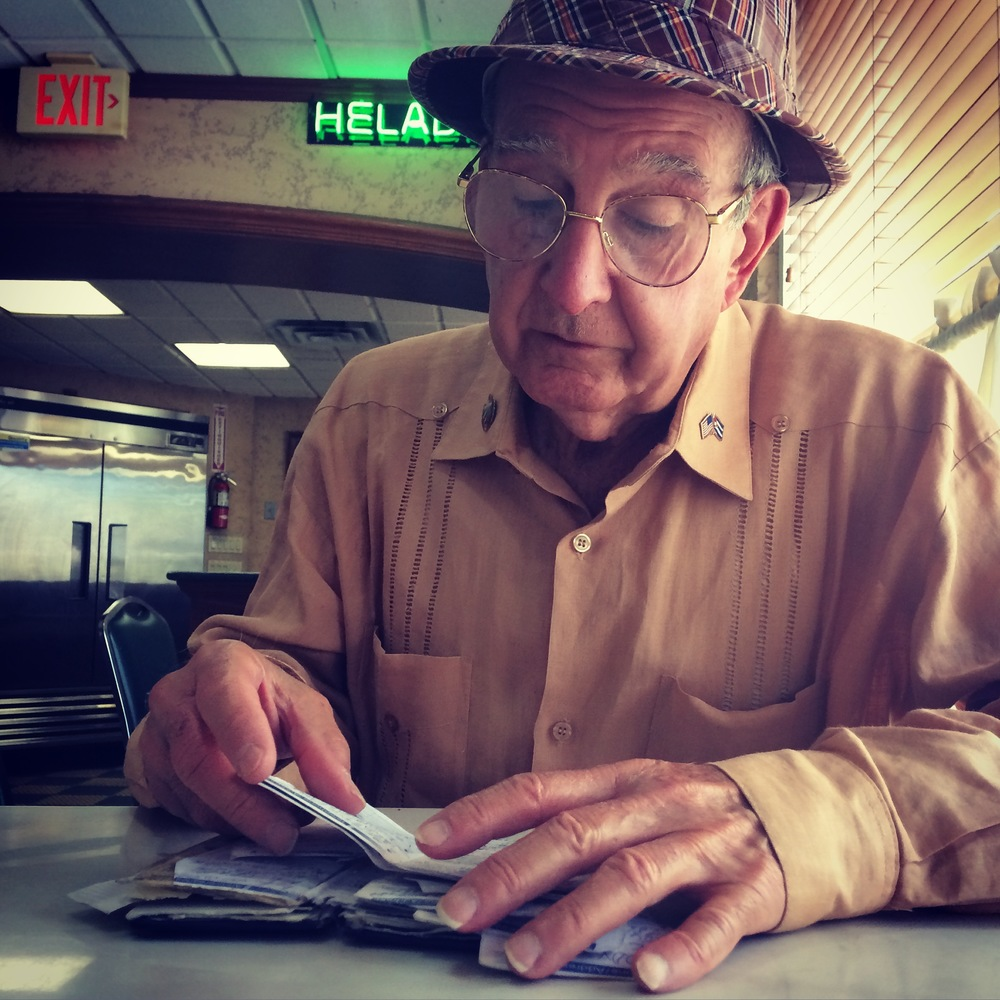 a cuban-american make looks through his documents at a miami cafe. photo credit: christine amario for the alignist.
