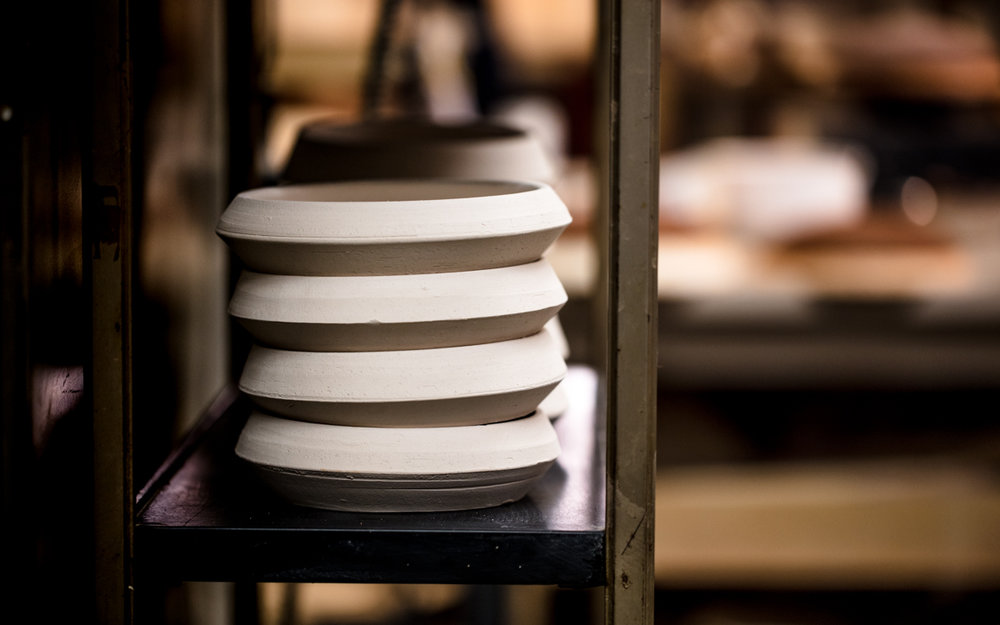 Stacked wheel-thrown 'greenware' waiting to be bisque fired