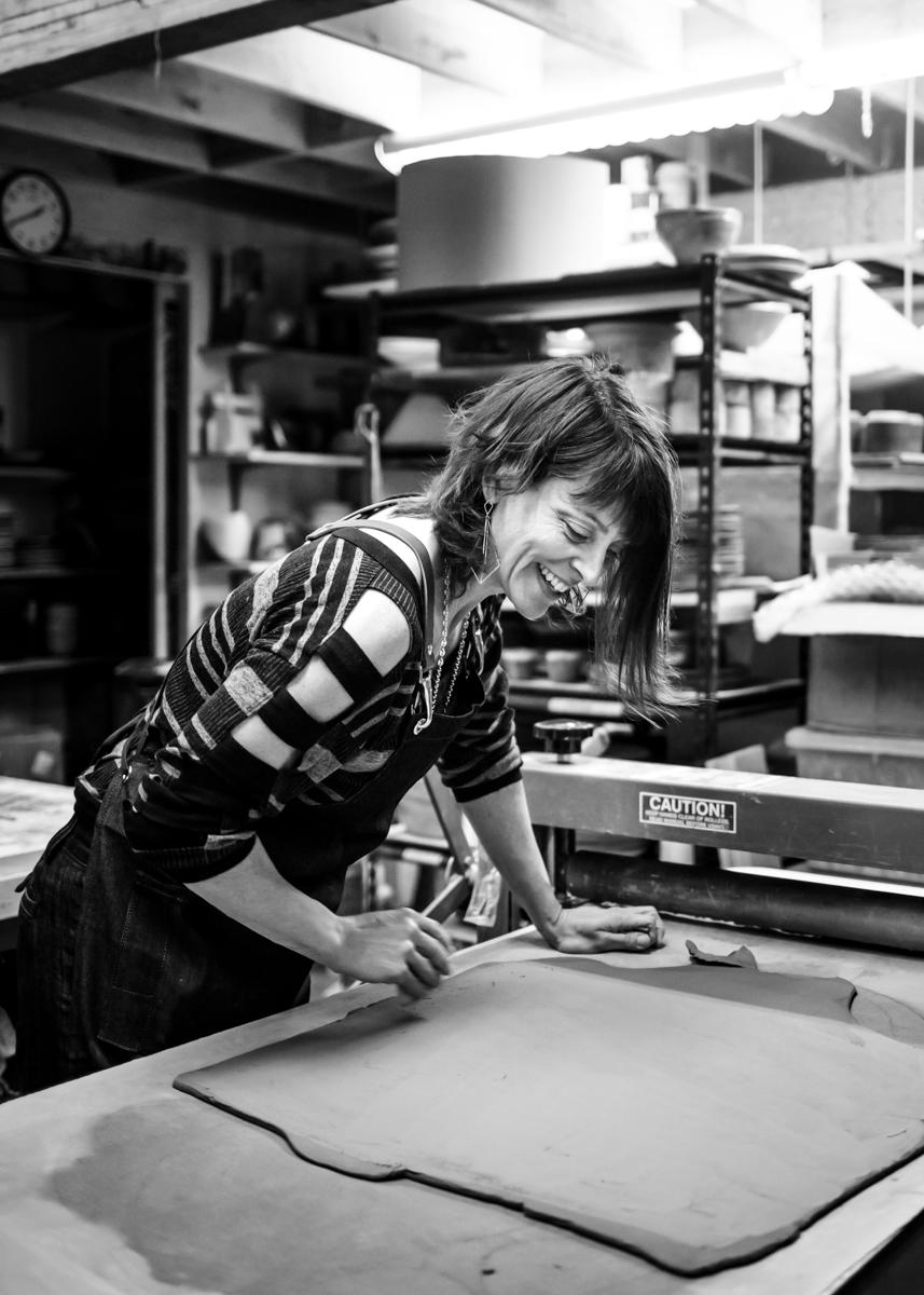 MaryMar Keenan using a rib to smooth the surface of a clay slab