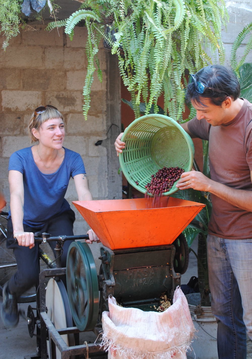 Grand Central Bakery's Jess Tannenbaum and Nossa Familia owner & founder Augusto Carneiro try out a bicycle coffee mill in Guatemala.