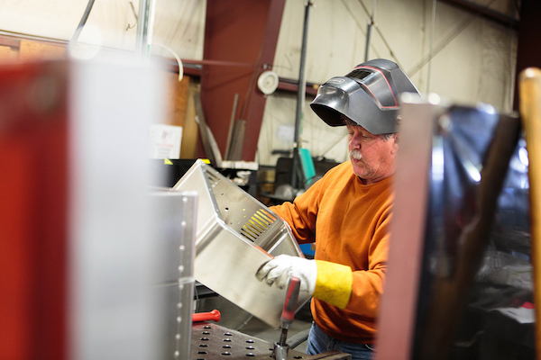 Copy of Craftsman inspecting the hand welds on the MediaBooth Pro enclosure