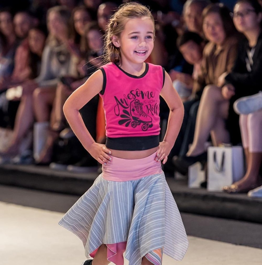 "This cutie told me right before she hit the runway...""I'm going to show some attitude out there!""  And she did...it included a few twirls for the photographers at the end of the runway!"