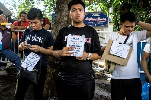 Men on Kalaw Avenue in Manila advertised seafaring jobs in September. Photo credit: Hannah Reyes for  The New York Times .