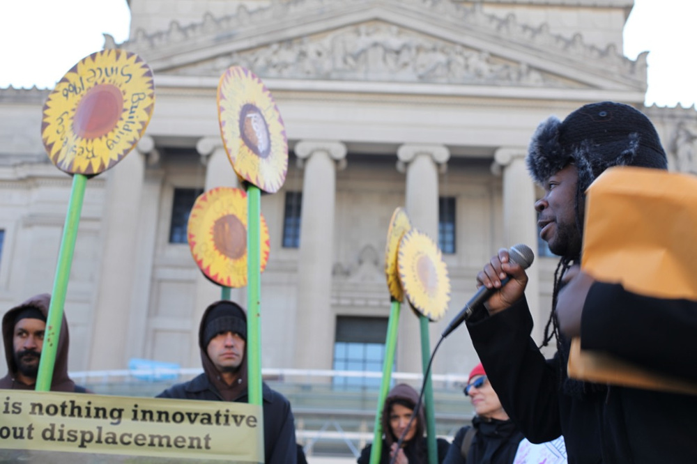 Imani Henry speaking at the protests at the Brooklyn Museum on Tuesday, Nov. 17th. Photo by Isaac Kaplan. Taken from Artsy.