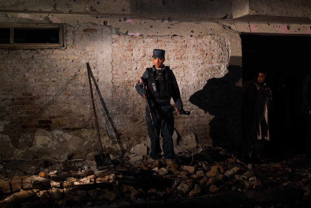 An Afghan National Police officer stands in the rubble of a suicide attack in the Kabul neighbourhood of Taimani. 2017.