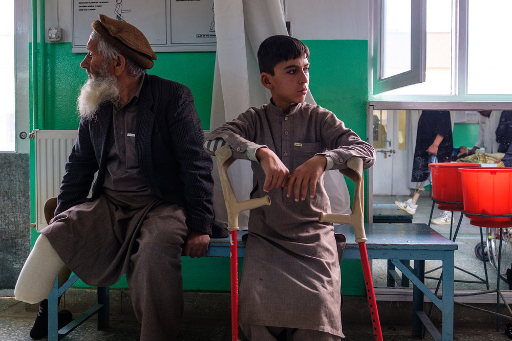 Two generations of land-mine victims waiting to be fitted for prosthetics at the ICRC clinic in Kabul. 2018.