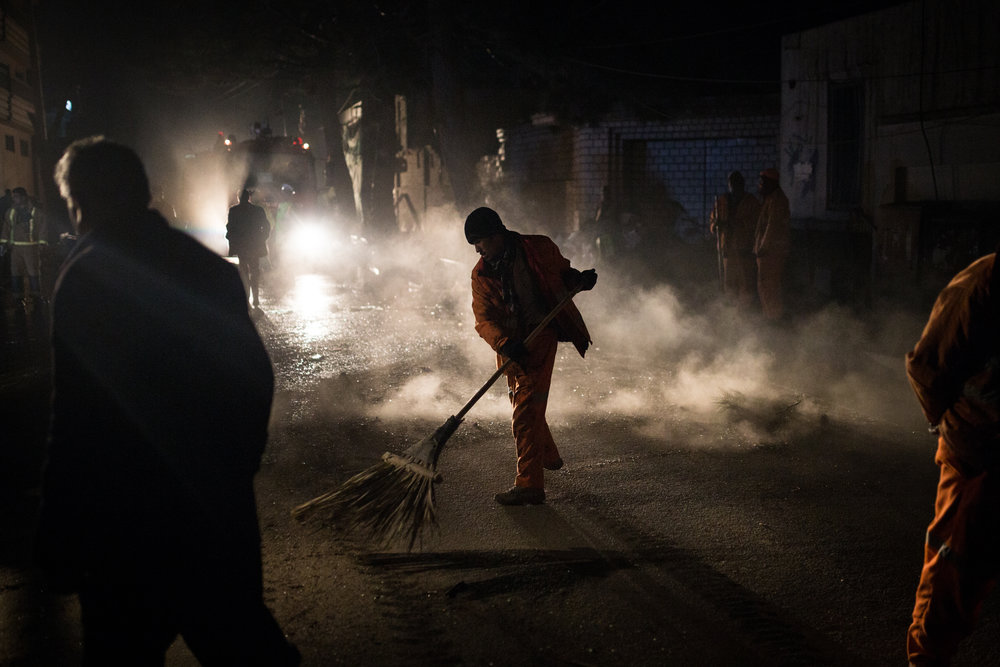 A municipal worker sweeps debris off the street following a suicide attack in the Kabul suburb of Taimani. 2017