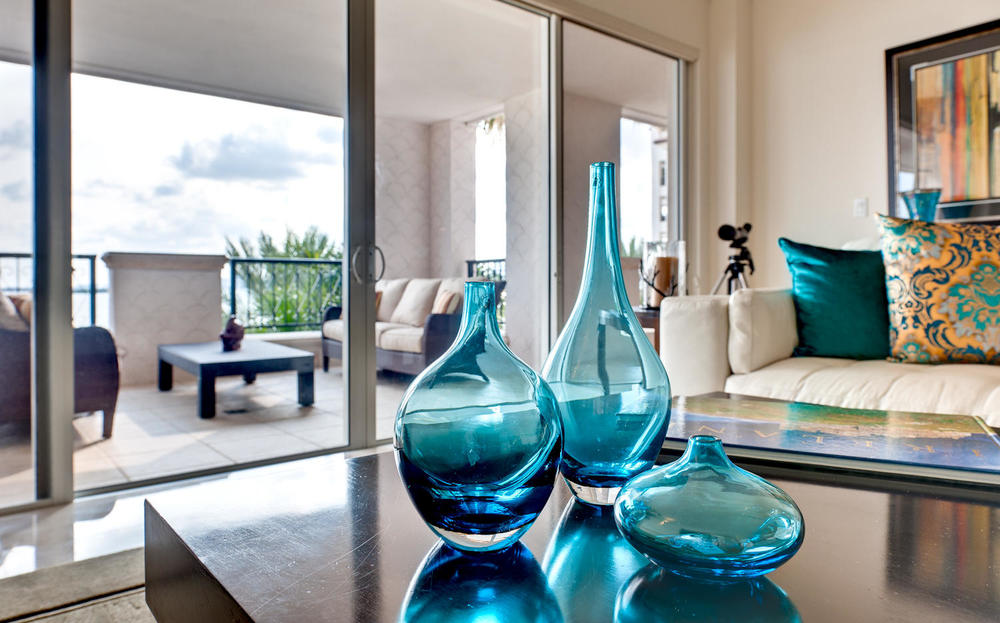 Design & Decor by Captiva Design; striking aqua bottles in modern, white room with bright, colorful accent pieces.