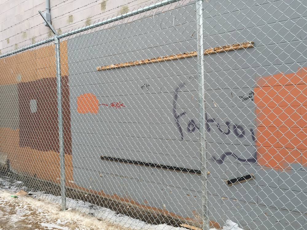 The MoTA piece that was placed on this building was removed during the installation of the chain link fence.
