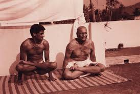 Jois, on the right, with his grandson Sharath, lifting up into  Utpluthih.