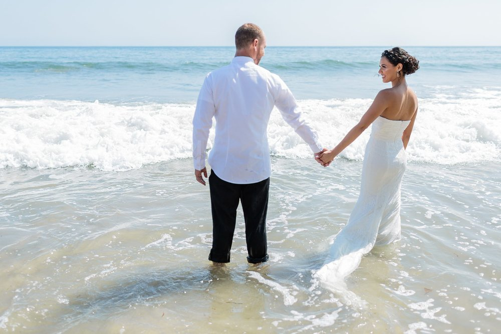 bride and groom in the ocean santa barbara