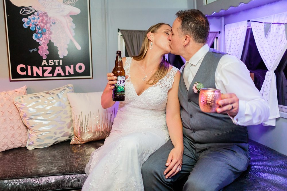 bride and groom kiss in vintagique bar trailer