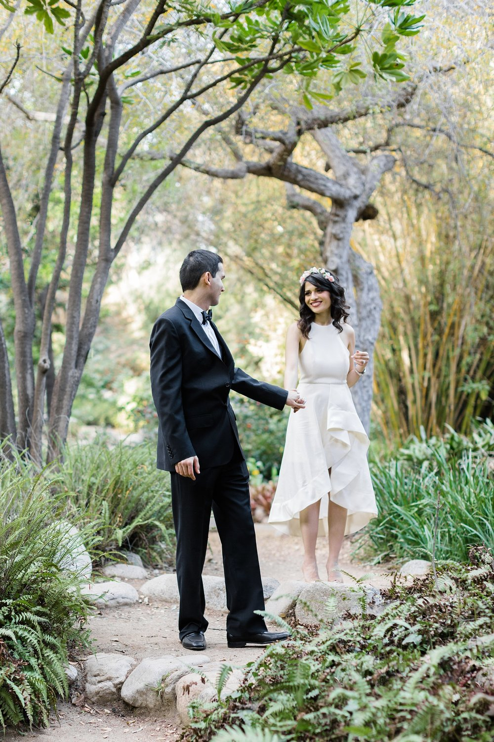 groom leading bride through botanical garden