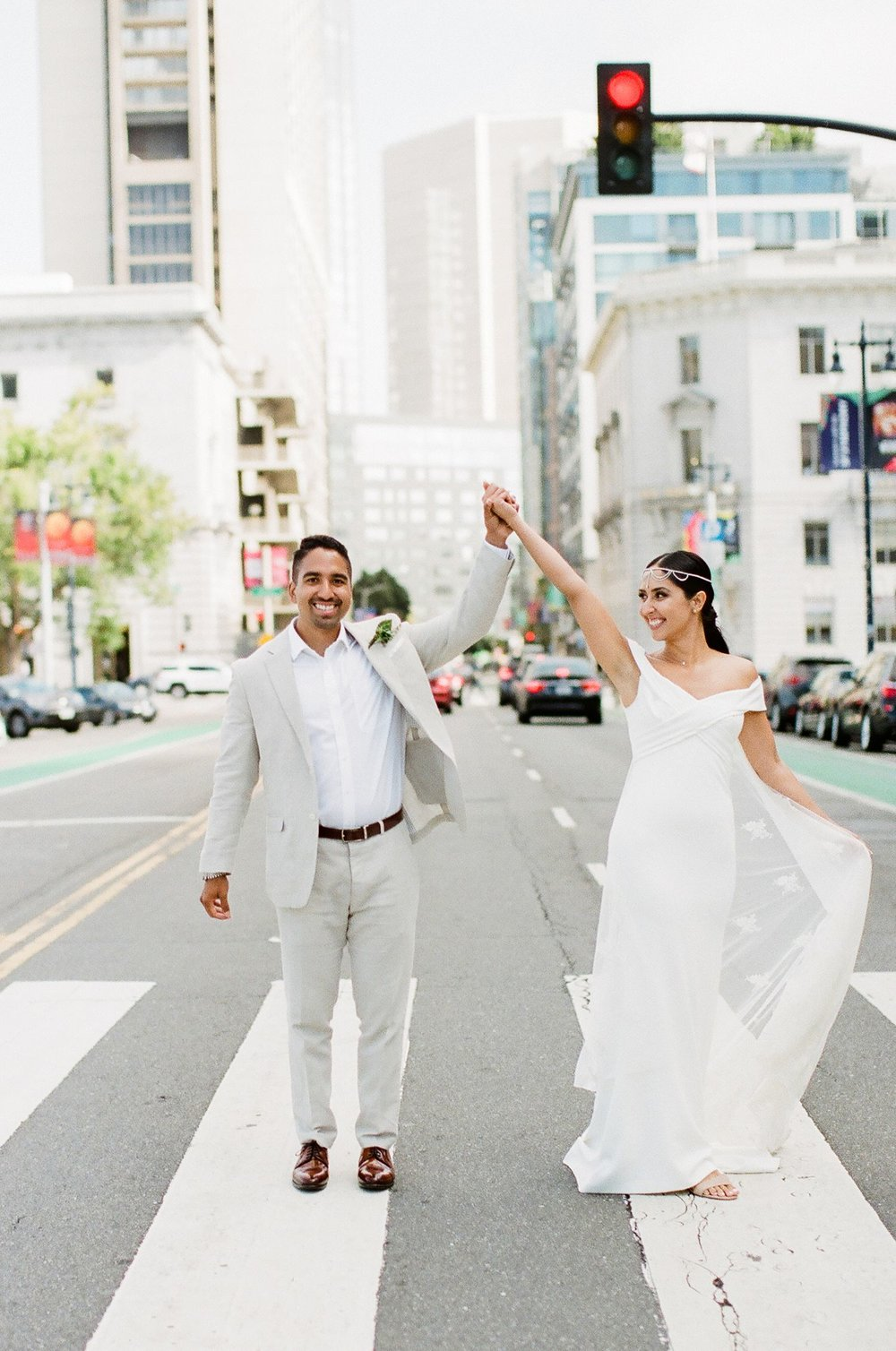 bride and groom hold hands in middle of san francisco street