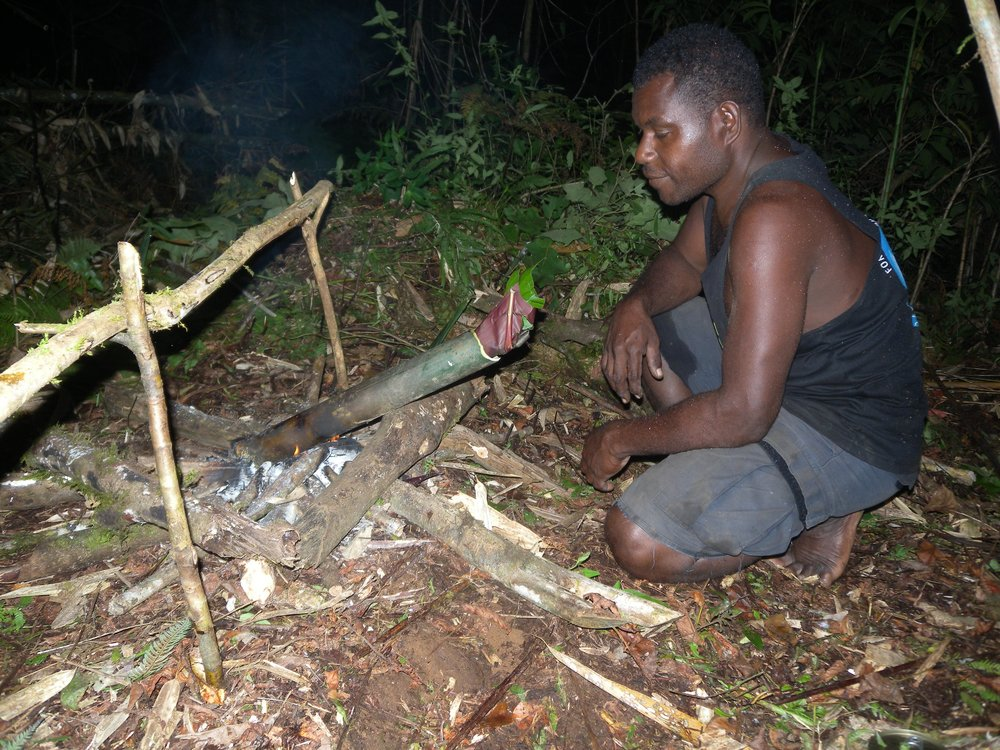 Stanley Mapaniata cooking kasume, harvested from the forest, using bamboo as a cooking pot.