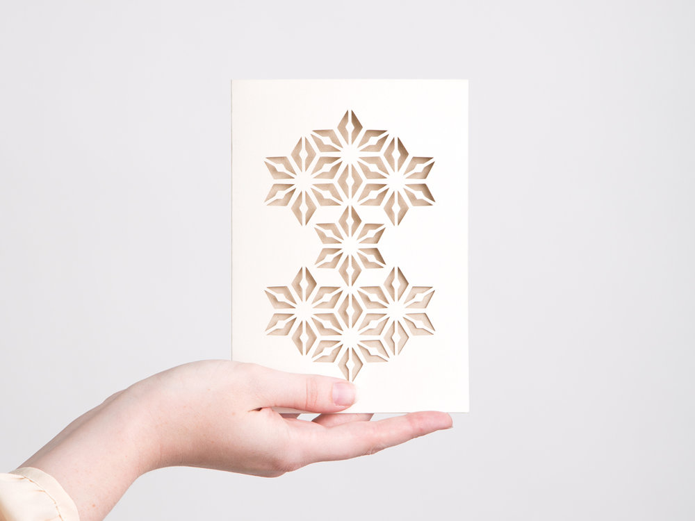 If you're looking for a unique card, this could be a great design for you. This design features a silver pearlescent paper with cut-outs that reveal a kraft paper insert. It's a delicate card that just about anyone would appreciate receiving.