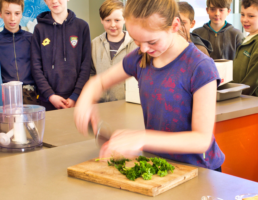 Abby shows her knife skills by chopping up parsley