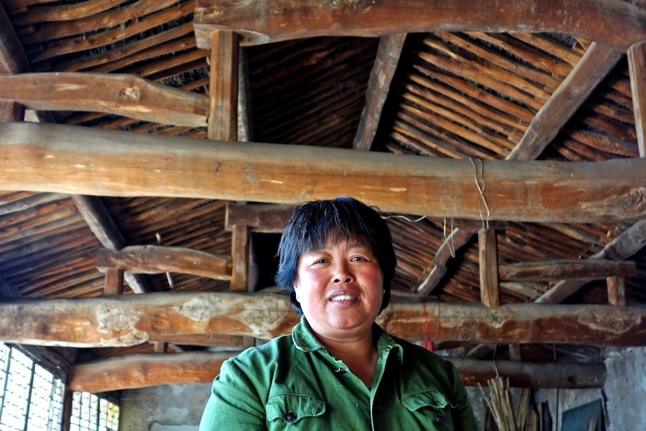 Song Xiu'e under a traditional roof in a large hall at her guesthouse.