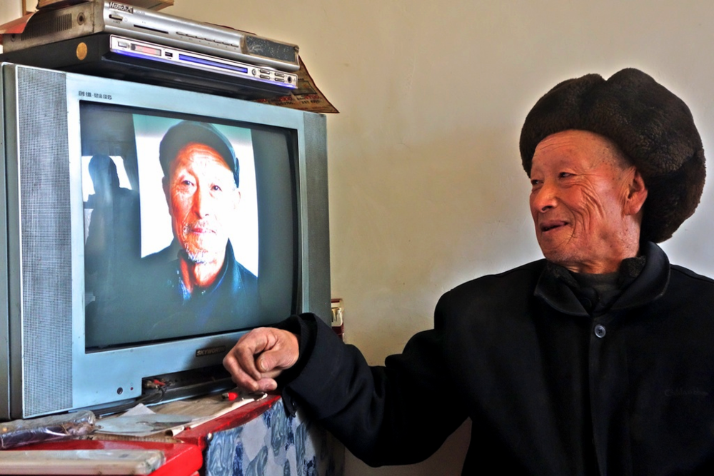 Li Shizhang looking at a photo of himself.