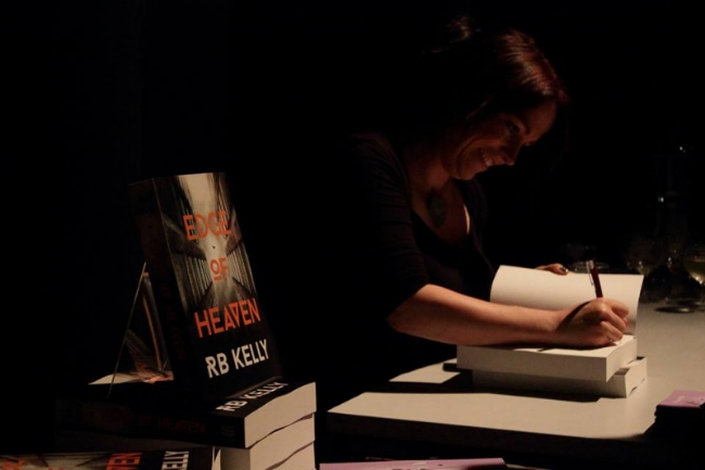 Signing one of many copies of Edge of Heaven bought at the launch